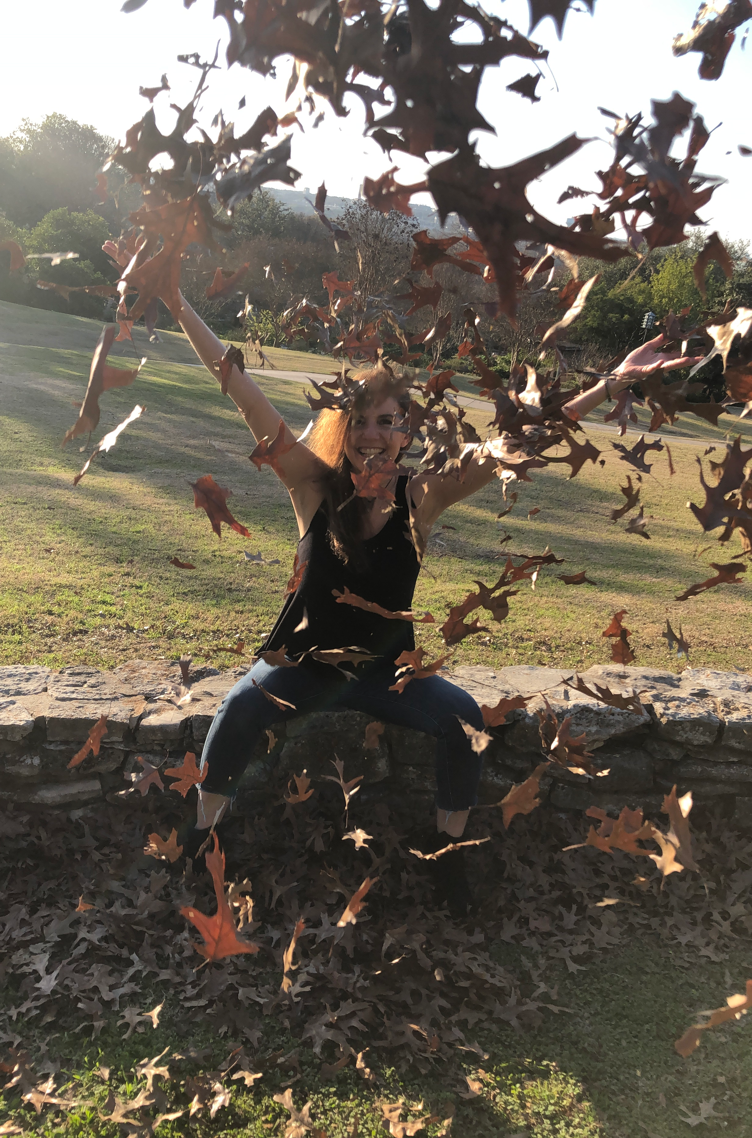 Leslie throws fall leaves into the air & they fall, dancing in the breeze